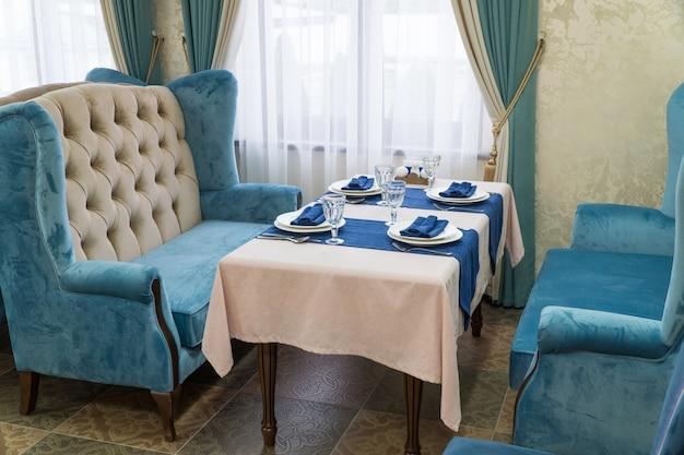Обслуживание банкетного стола в роскошном ресторане в голубом и светлом стиле.