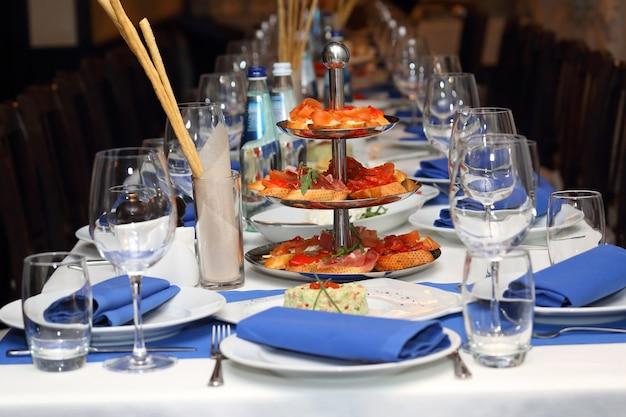 青と白のスタイルでレストランで宴会テーブルを提供