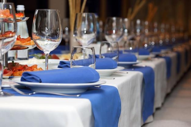 青と白のスタイルでレストランで宴会テーブルを提供しています