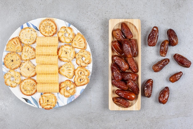A serving of biscuits on a painted platter with a pile of dates on and next to a wooden tray on marble surface