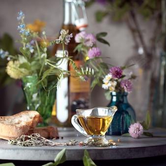 향신료와 야생화 사이에 올리브 오일 한 그릇 제공 프리미엄 사진