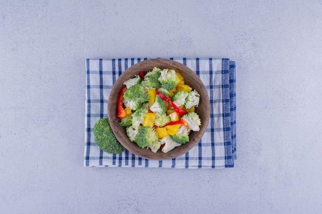 Servizio di broccoli e insalata di peperoni in una ciotola su un asciugamano piegato su sfondo marmo. foto di alta qualità