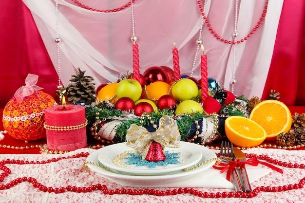 白と赤の生地の背景にクリスマステーブルを提供しています