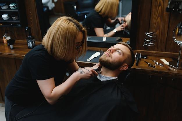 Serving client in barbershop. professional barber girl, female hairdresser making modern haircut for a man sitting in barber shop chair.