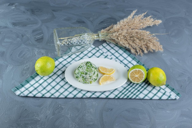 Serving of cooked rice with lemons on a folded tablecloth, next to a decorative bundle of feather grass stalks on marble table