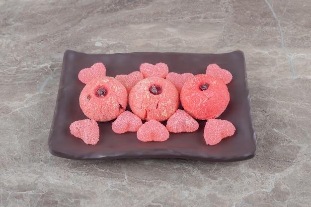 Servizio di biscotti e caramelle gommose su un piatto su superficie di marmo