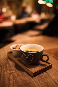 木製のトレイにラスクのカップと一緒にカップでクリームスープを提供しています。