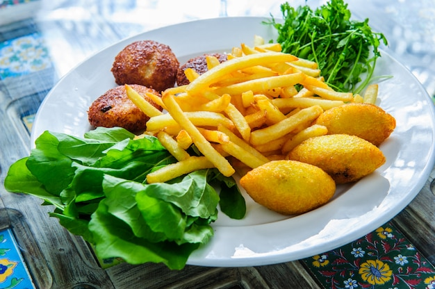 Serving of falafel and chips served on a black plate with sauce.