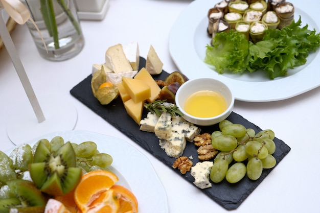 Serving a festive table with a variety of dishes. pieces of cheese of different varieties, honey in a glass bowl, fruits, vegetables and nuts on a ceramic black dish on a light table.