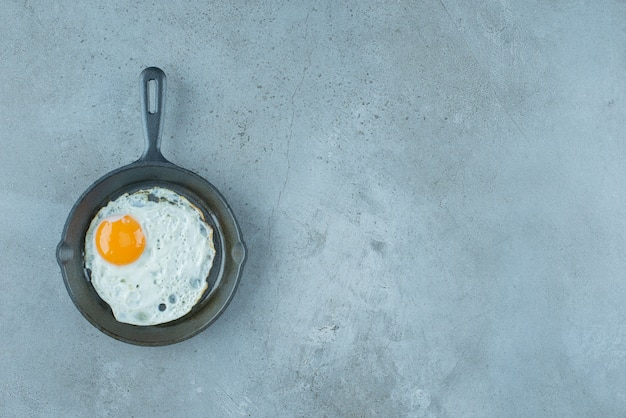 A serving of fried egg in a pan on marble background. high quality photo