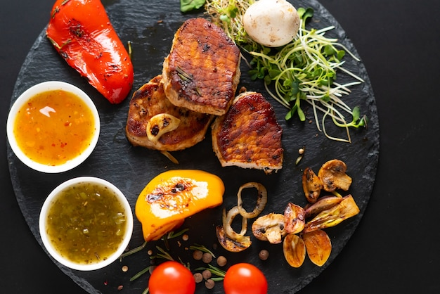 Serving of grilled pork fillet with assorted roast vegetables, tomatoes, dipping sauce and salad sprouts viewed from overhead on a black board