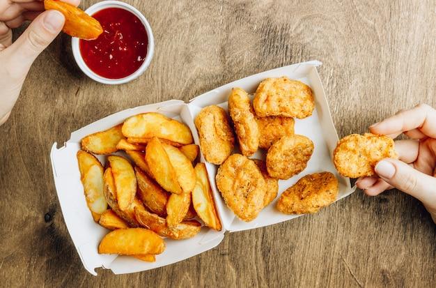 Подавать в бумажной коробочке с самородками с жареным картофелем и соусом.