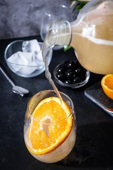 Подача чайного гриба с лимоном и имбирем в стакане с долькой апельсина