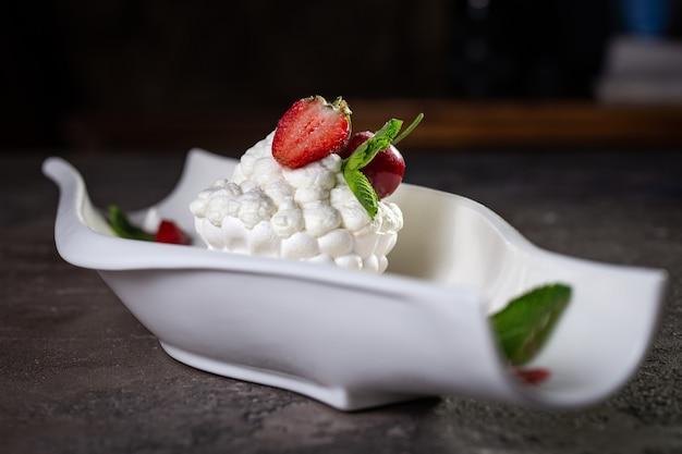 Подача десерта из безе с клубникой в белой тарелке