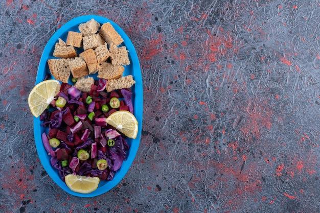 Подача салата из свеклы и краснокочанной капусты с вяленой корочкой и гарниром из ломтиков лимона на темном фоне. фото высокого качества