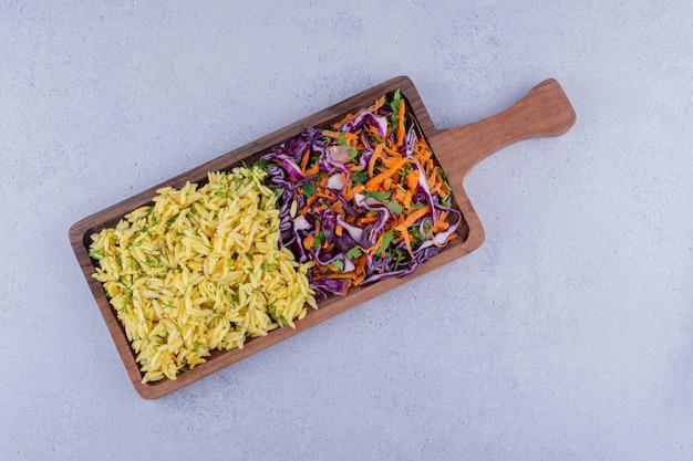 Подача коричневого риса и салата из красной капусты в подносе на мраморном фоне. фото высокого качества