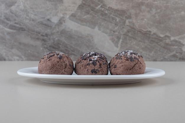 大理石の背景の大皿にチョコレートクッキーのサービング。