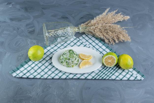 Подача вареного риса с лимонами на сложенной скатерти рядом с декоративным пучком стеблей ковыля на мраморном столе