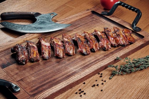 Сервировка очень вкусных жареных свиных ребрышек барбекю на деревянной доске. пивная закуска. вид сверху еды