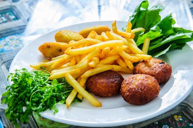 Порция фалафеля и чипсов подается на черной тарелке с соусом.