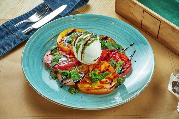 나무 테이블에 파란색 접시에 파스타와 발사믹 소스와 토마토와 부라 타 치즈의 다른 유형에서 신선한 샐러드 제공. 식당 테이블 설정