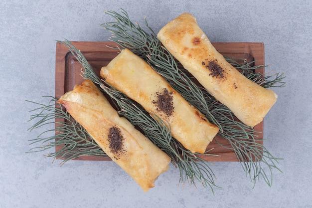 Подача русских блинчиков на деревянном блюде, украшенном сосновыми листьями на мраморном столе.