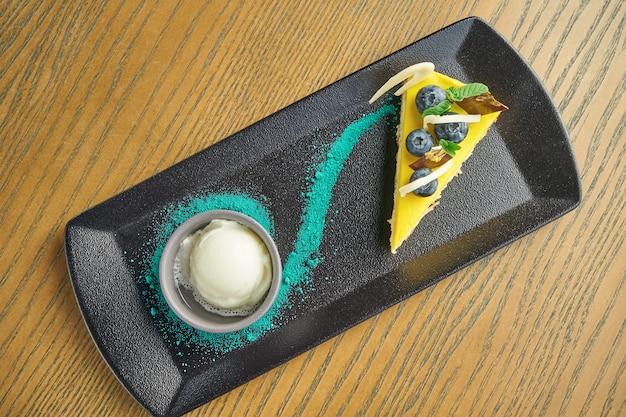 木製のテーブルの黒い皿にジャムとおいしいチーズケーキを提供レストランのテーブルの設定。ビューを閉じます。ペストリーデザート