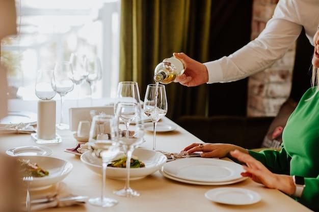 레스토랑에서 고객에게 화이트 와인 제공. 초점은 병과 유리에 있습니다.