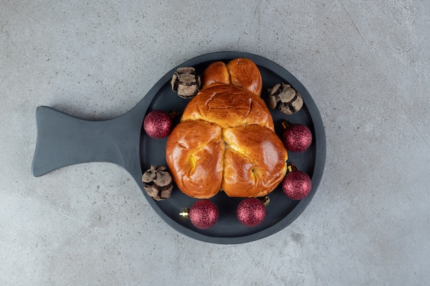 Serving pan holding christmas decor and a sweet bun on marble surface