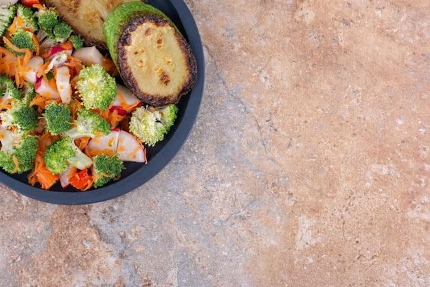 Сервировочная сковорода с обжаренными ломтиками кабачков и овощным салатом на мраморной поверхности