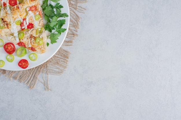 Una porzione di pizza con peperoni e foglie di prezzemolo su una superficie di marmo