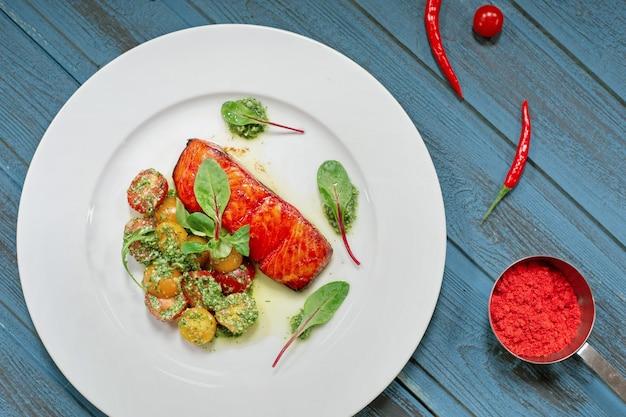 Сервировочное блюдо из лосося на гриле с овощами, базиликом, помидорами и соусом.