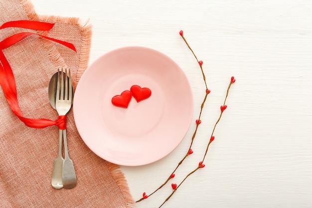 Сервировочная тарелка с сердечками. меню для романтического ужина в день святого валентина. сервировка стола.