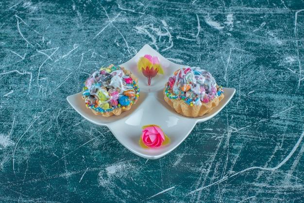Un piatto da portata con cupcakes e corolle di fiori su sfondo blu. foto di alta qualità