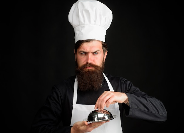 Serving and presentation cooking profession and people concept male chef cook holds cloche cook
