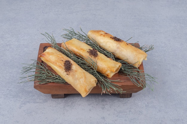 Serving of russian blins on a wooden platter, adorned with pine leaves on marble