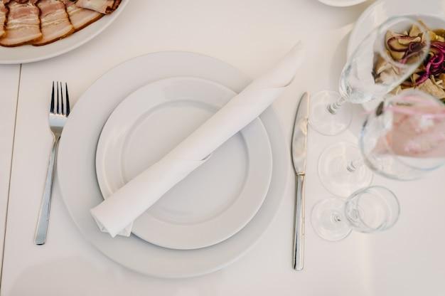 Сервировка, сервировка стола. тарелка и столовые приборы столовые приборы льняная салфетка белая. украшение свадебного стола. художественное произведение. вид сверху. закройте вверх.
