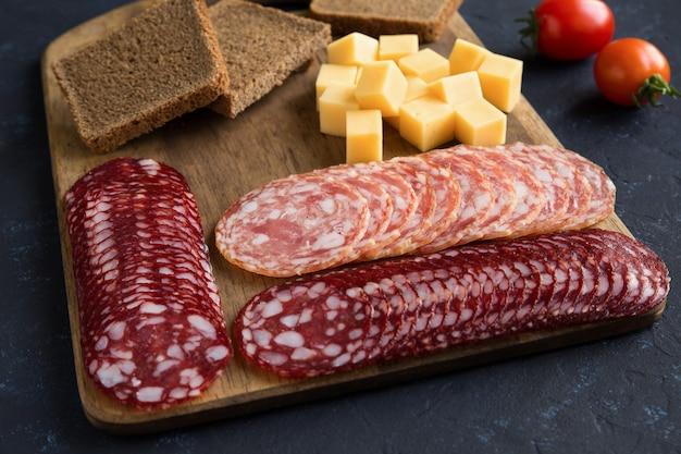 Подача ломтиков копченых колбас на деревянной разделочной доске с кубиками сыра и хлебом на темно-синем фоне