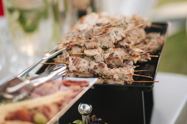 저녁 파티를 위한 뷔페 케이터링에서 작은 핫 치킨과 붉은 생선 케밥 제공