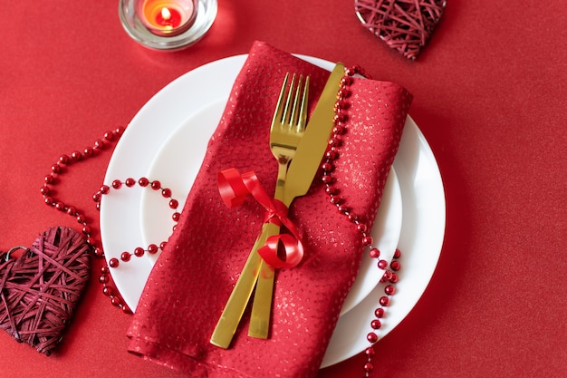 Serving table with fork, knife, napkin and heart decoration for valentine's .dinner on valentines day.