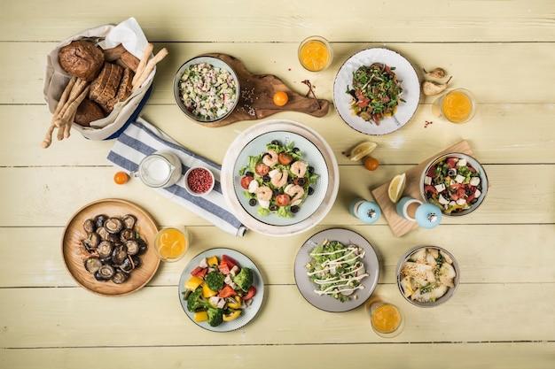 다양한 샐러드, 구운 버섯, 빵, 밝은 나무 배경에 안경에 상쾌한 음료로 만든 테이블을 제공합니다. 복사 공간이 있는 상위 뷰입니다. 수평 방향.