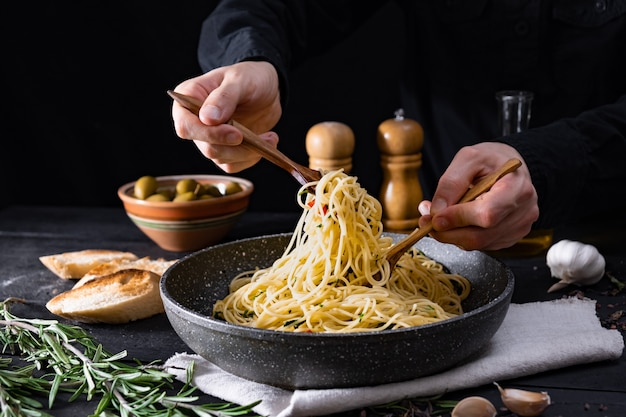 Serving traditional  italian pasta from a pan. male hands taking spaghetti in spoon and fork, shot in low key