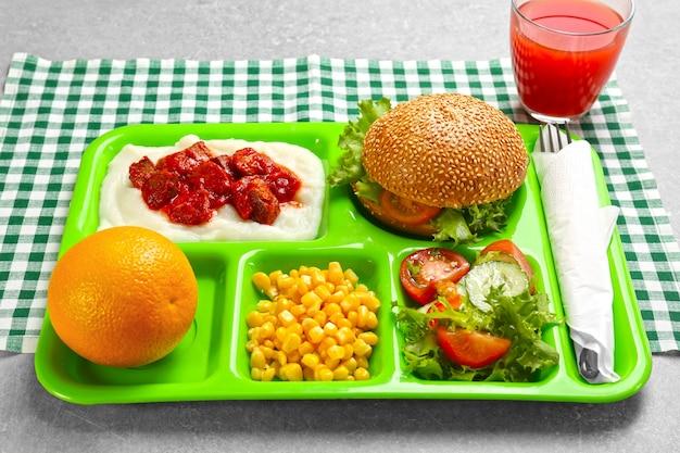 テーブルの上においしい料理が入ったサービングトレイ。学校給食の概念