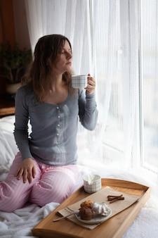 Сервировочный поднос со сладким десертом и чашкой кофе на кровати, белые простыни и одеяло в отеле