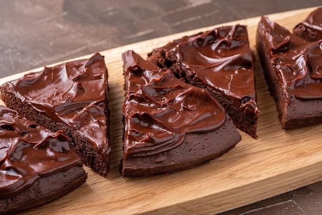 Сервировочные треугольные пирожные с кремом ганаш на сервировочной деревянной доске. закройте