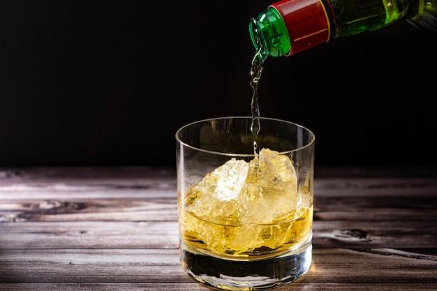 소박한 나무 테이블에 큰 얼음 덩어리와 함께 위스키 잔에 있는 병에서 위스키를 제공합니다. 공간을 복사합니다.