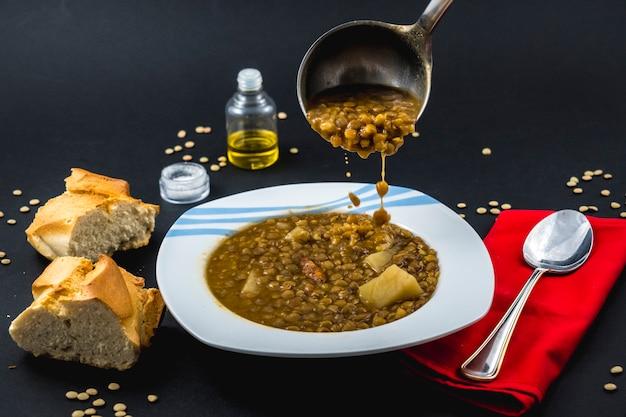 빵과 함께 먹을 준비가 된 스페인 렌즈 콩 접시에 냄비와 함께 제공