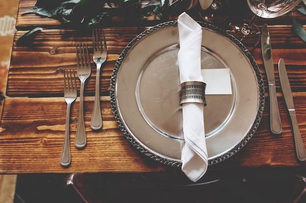 銀のプレートと花で飾られた木製のテーブルを提供
