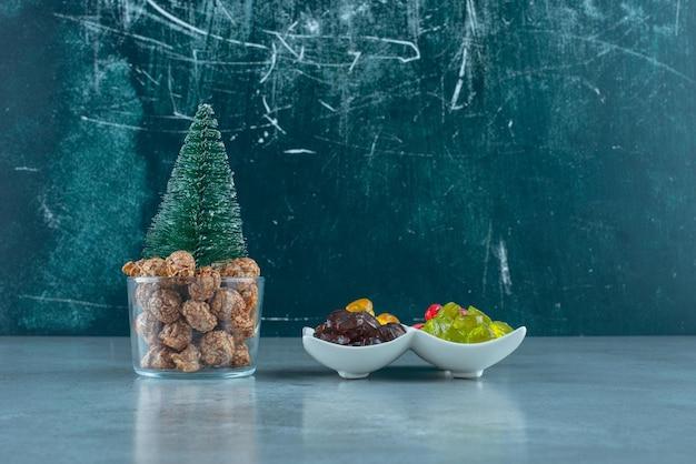 Порции карамели и попкорна, порции леденцов на мраморе.