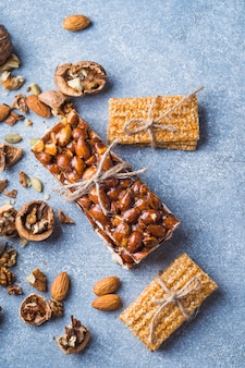 Sesame and almonds healthy bar tied with string on concrete backdrop